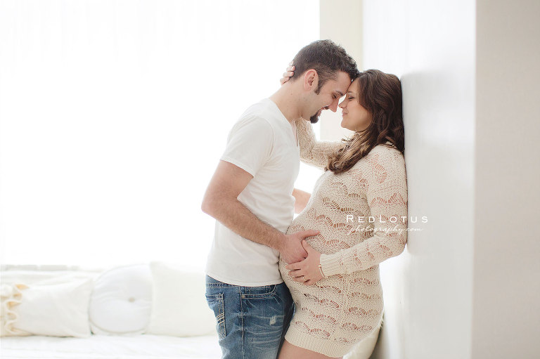 Maternity photography - young couple, lace sweater, white shirt, jeans, natural light bedroom