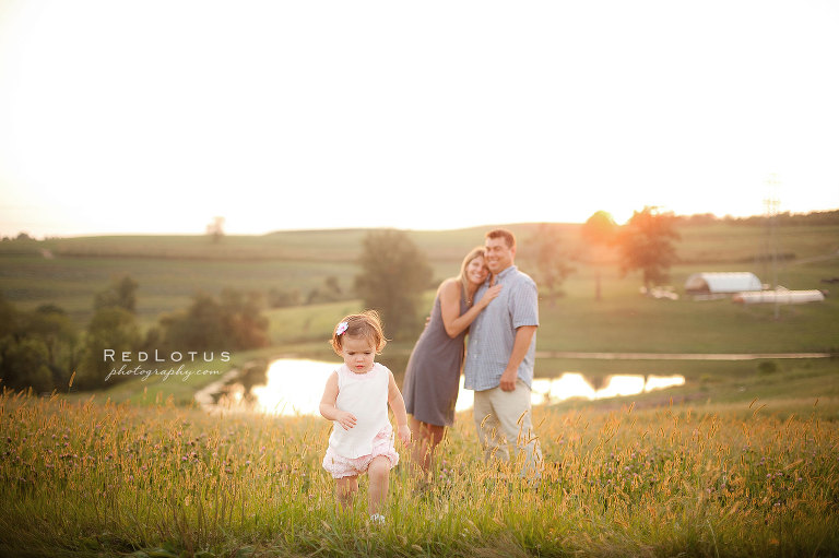 Family photography in a grassy field at sunset on a farm with a lake