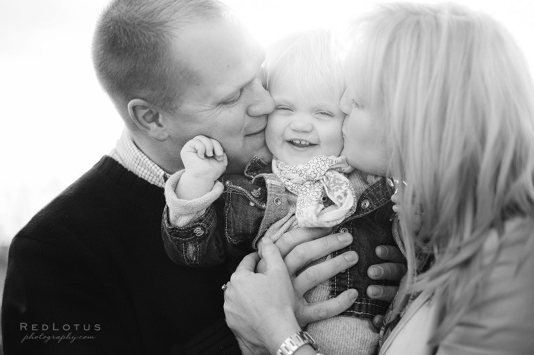Family photography parents kissing child