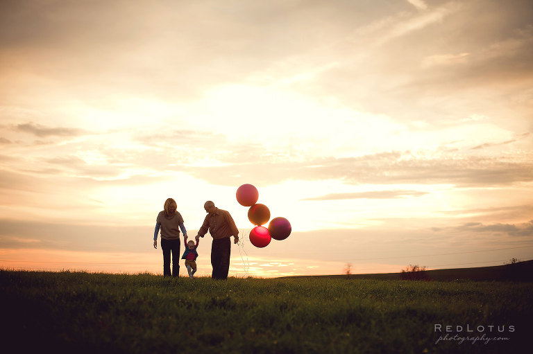 Family photo session outdoors with balloons at sunset